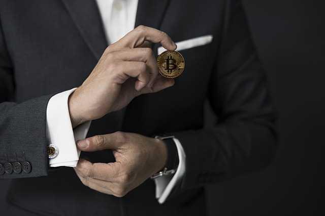 Мужчина держит монету биткоин